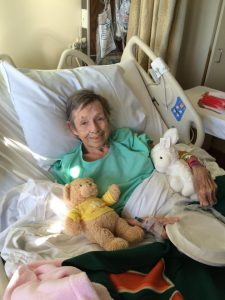 My Mom in a hospital bed holding a teddy bear